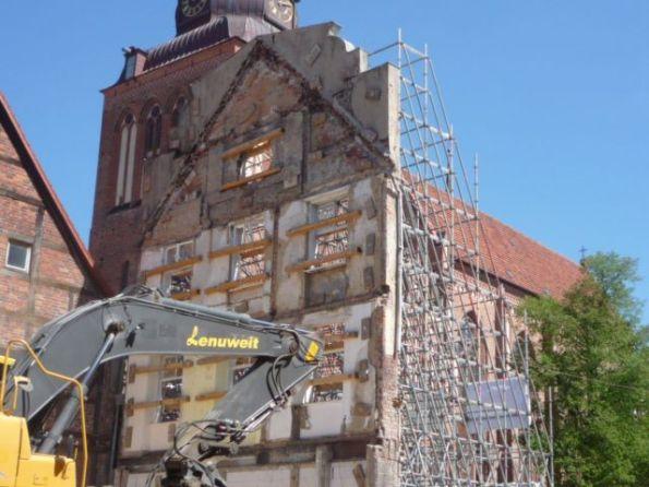 Eine Fassade, die einem fast leidtun kann. Dahinter die Pfarrkirche